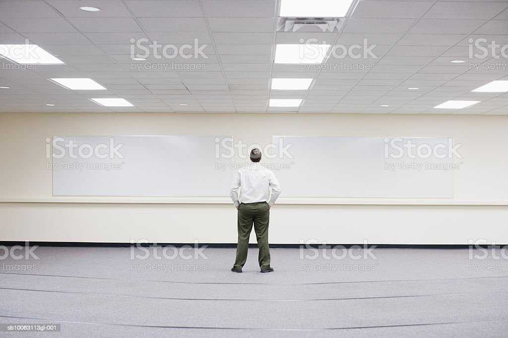 Businessman standing in large empty office room, rear view foto de stock royalty-free