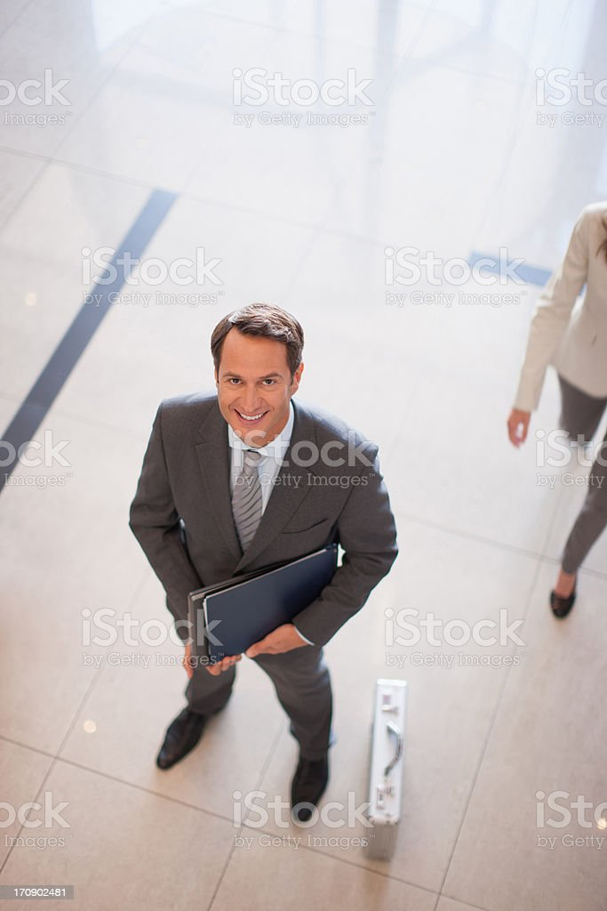 Businessman standing in lobby with briefcase royalty-free stock photo