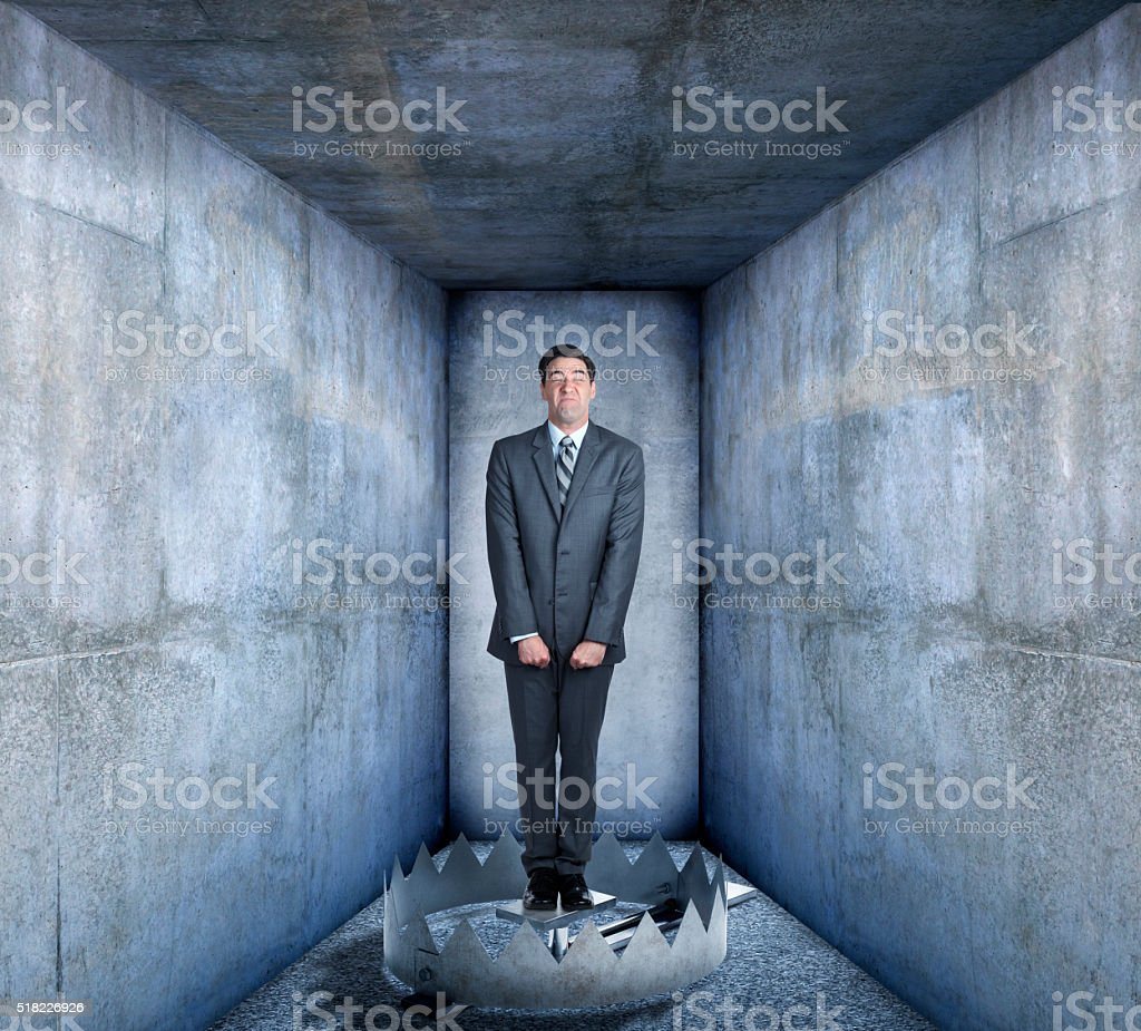 Businessman Standing In Middle Of Bear Trap stock photo