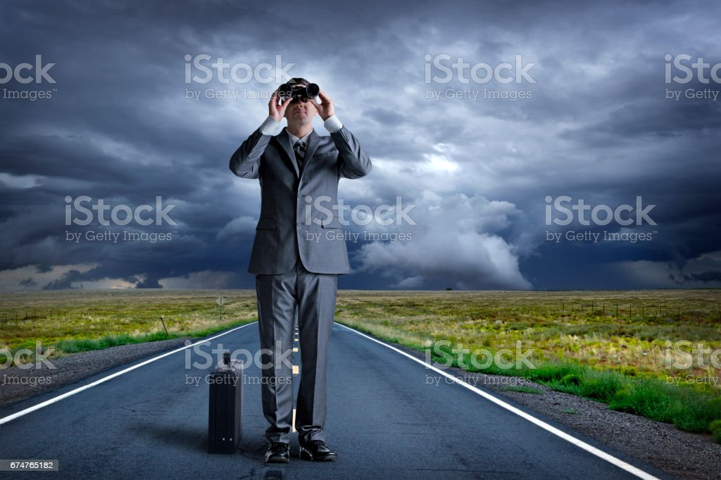Businessman Standing In Middle Of Road Looking Through Binoculars stock photo