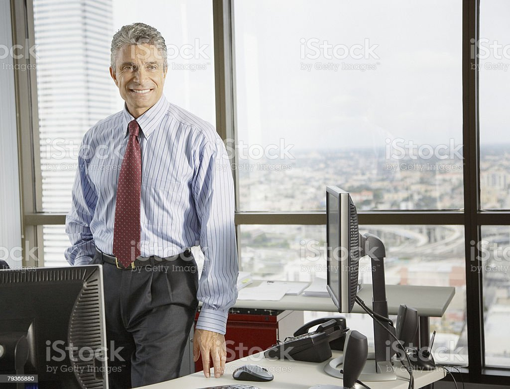 Businessman standing in office by large windows royalty-free stock photo