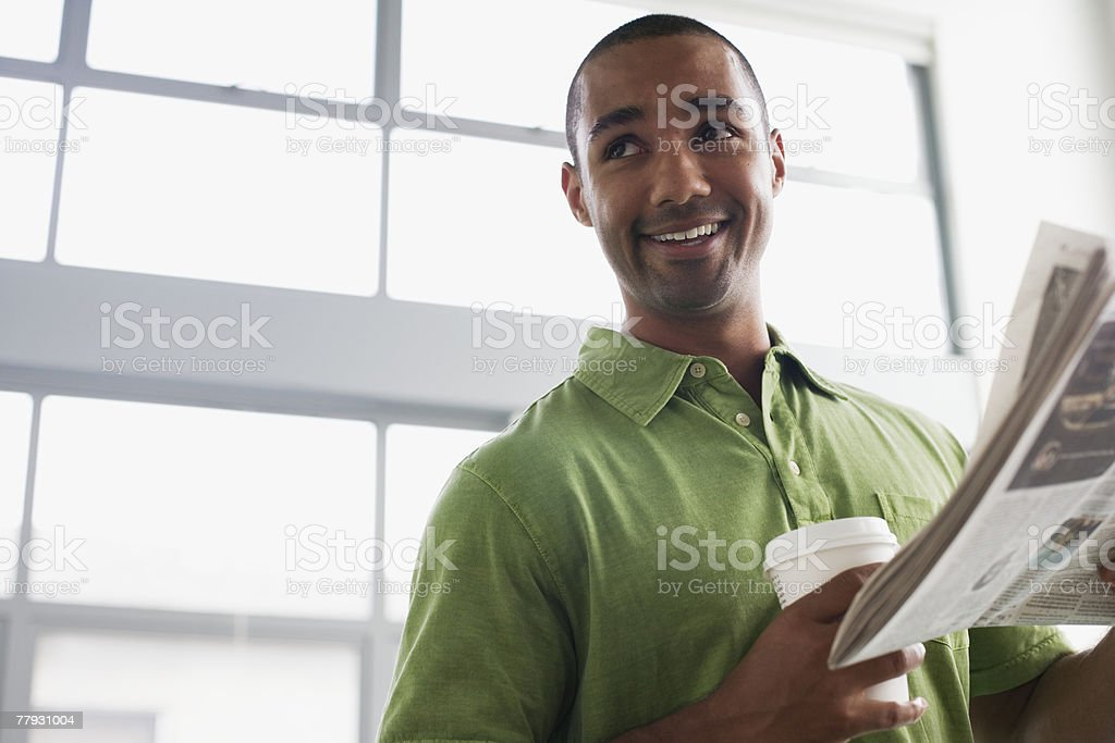 Businessman standing in office holding coffee cup and newspaper stock photo