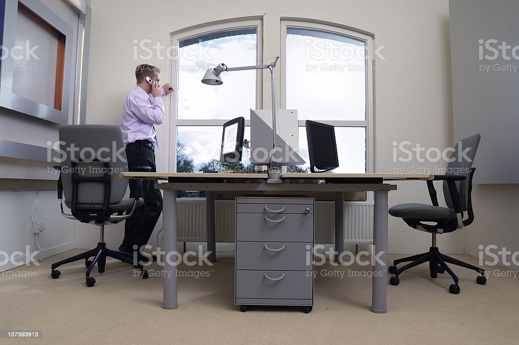 businessman standing in office talking on the phone royalty-free stock photo