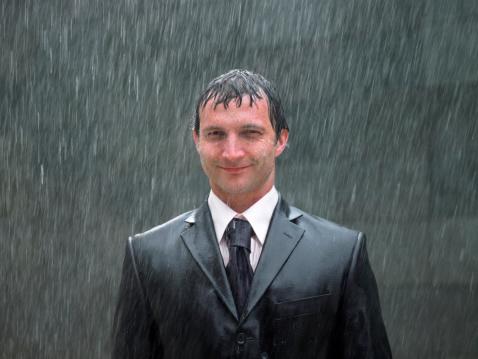Businessman standing in rain, smiling, portrait, close-up