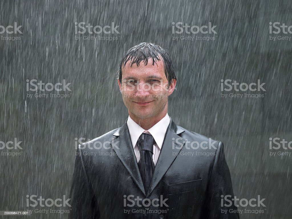 Businessman standing in rain, smiling, portrait, close-up stock photo