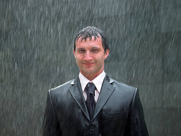 businessman standing in rain, smiling, portrait, close-up - wet stock pictures, royalty-free photos & images