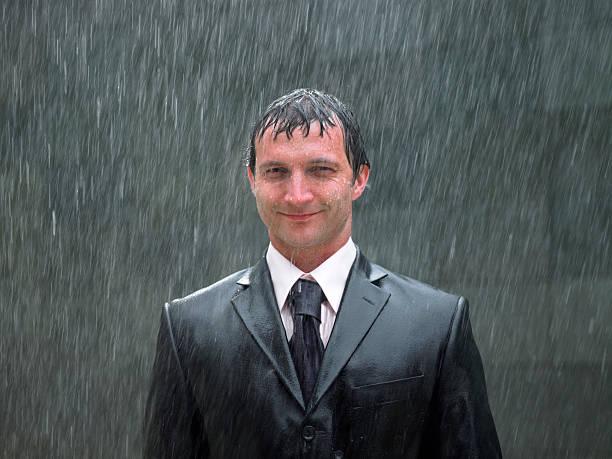 Businessman standing in rain, smiling, portrait, close-up stock photo
