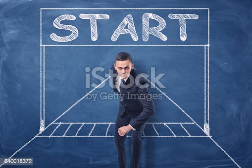 istock Businessman standing in running position on blue blackboard background with 640018372