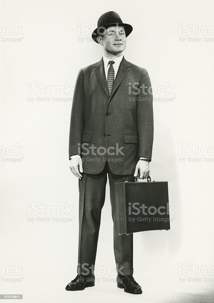 Businessman standing in studio, (B&W), portrait royalty-free stock photo
