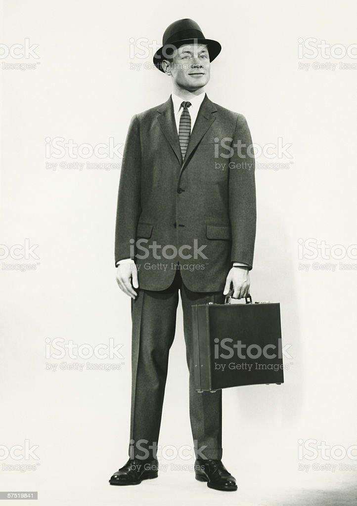 Businessman standing in studio, (B&W), portrait stock photo