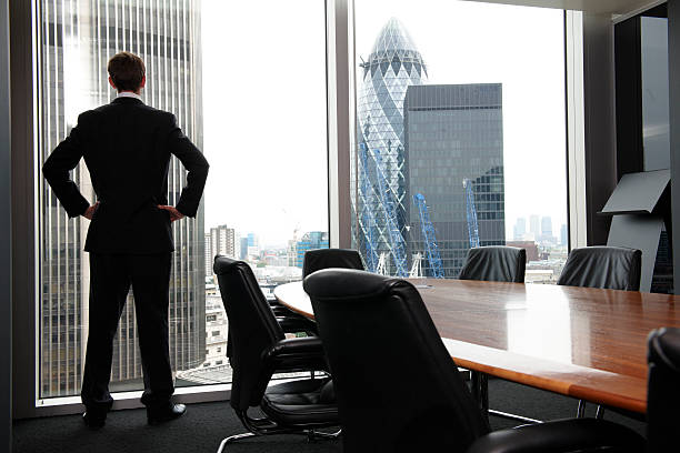 A businessman standing in the board room looking outside stock photo