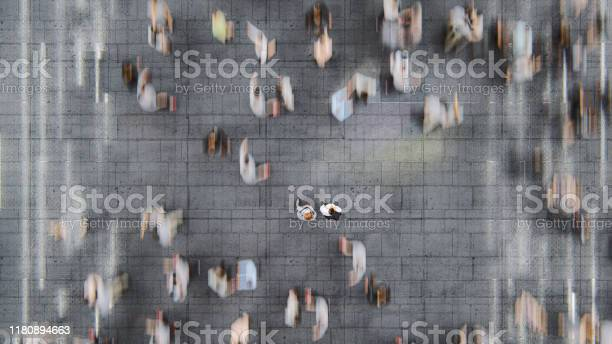 Photo of Businessman standing in the fast moving crowds of commuters
