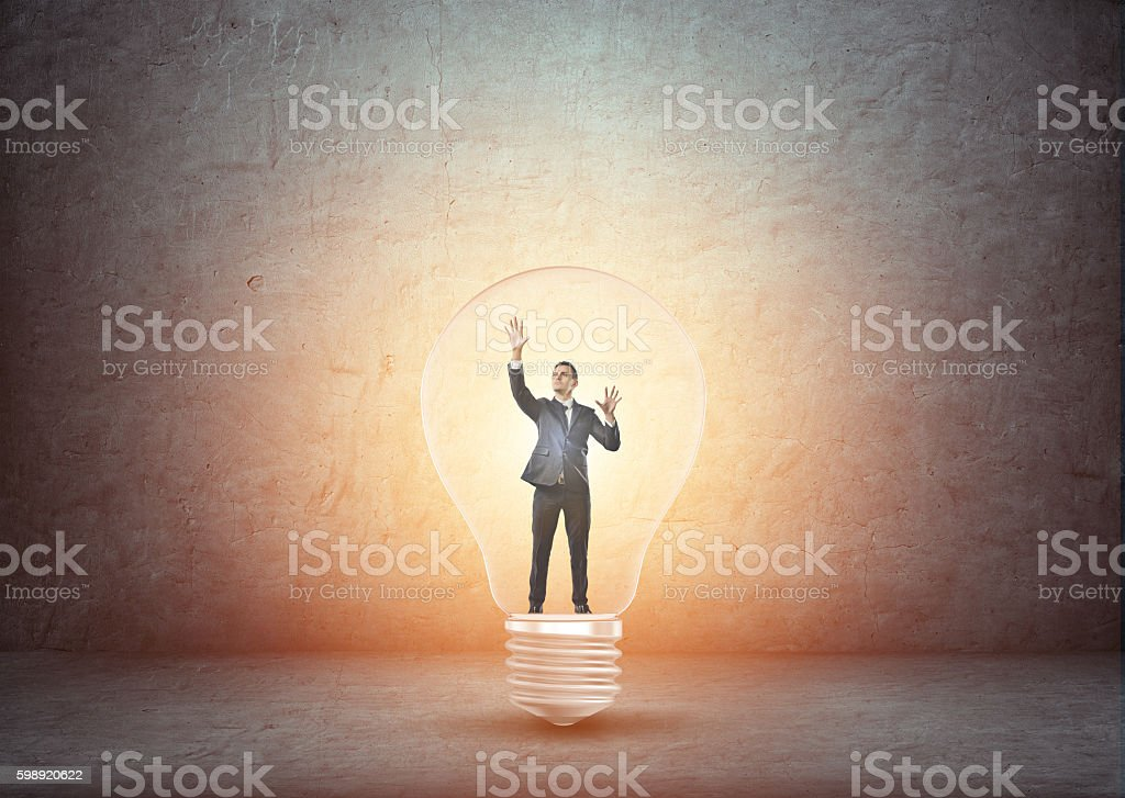 Businessman standing inside big glowing light bulb stock photo