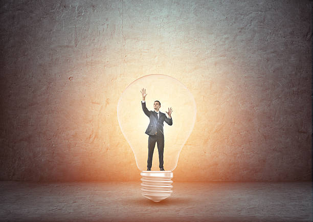 businessman standing inside big glowing light bulb - trapped stock pictures, royalty-free photos & images