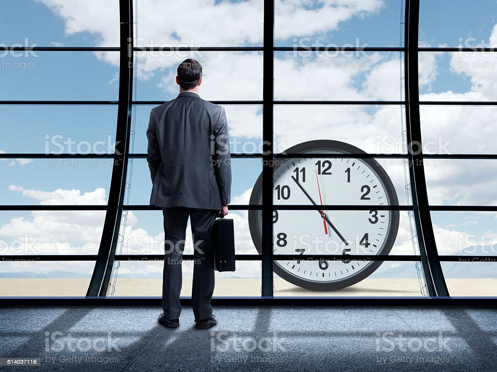 Businessman Standing Inside Office Building Looking Out At Clock stock photo