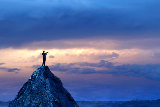 Businessman Standing Looking Through Spyglass On Mountain Peak A silhouetted businessman stands on top of a mountain peak and looks into the distance with a spyglass in front of a dramatic sunset in the distance. opportunity stock pictures, royalty-free photos & images
