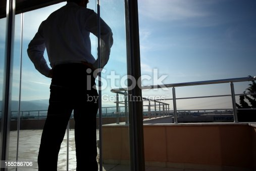 istock A businessman standing near a glass door 155286706
