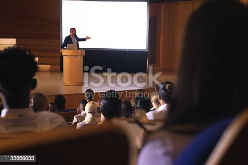 1133973551 istock photo Businessman standing near podium and giving presentation on white projector in the auditorium 1133856033