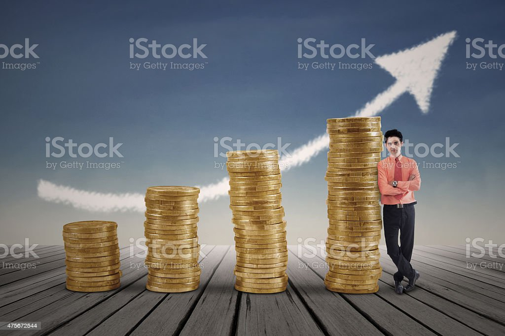 Businessman standing next to gold coins growth chart stock photo