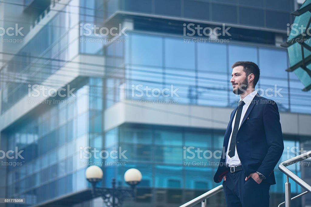 Businessman standing on background of buildings with glass facades Businessman in a suit standing on the background of the building with glass facades Adult Stock Photo