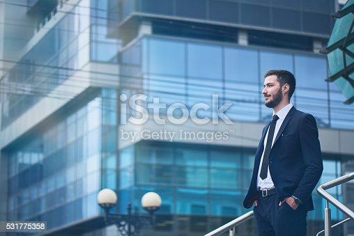 istock Businessman standing on background of buildings with glass facades 531775358