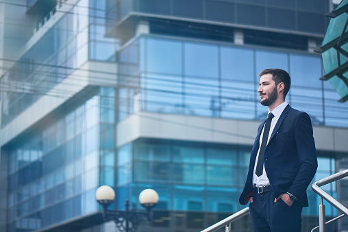 Businessman Standing On Background Of Buildings With Glass Facades Stock Photo - Download Image Now