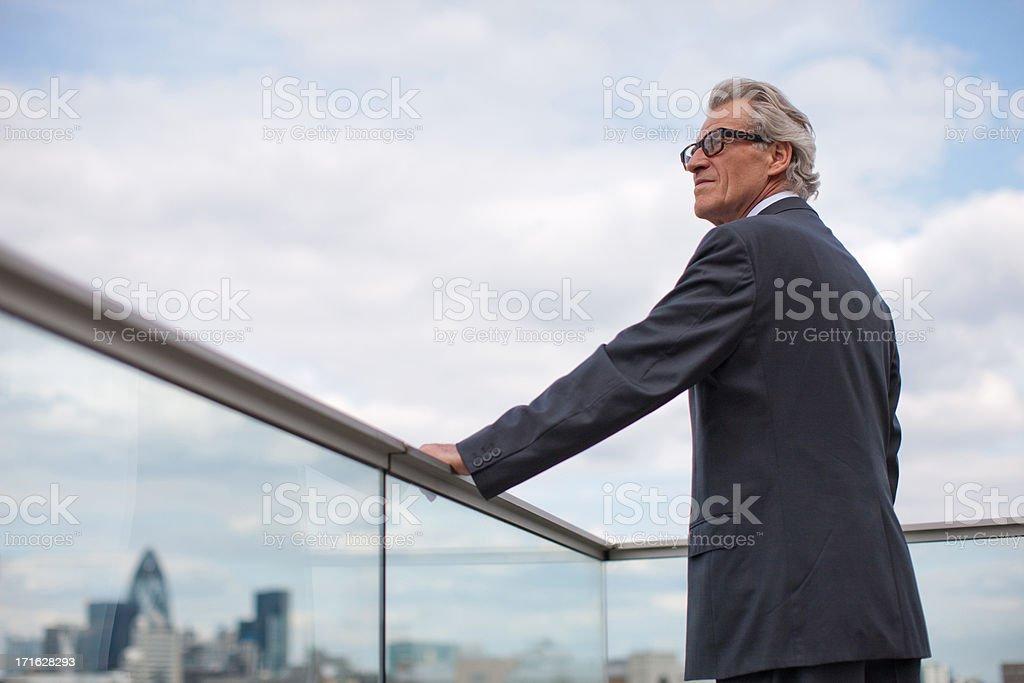 Businessman standing on balcony railing stock photo