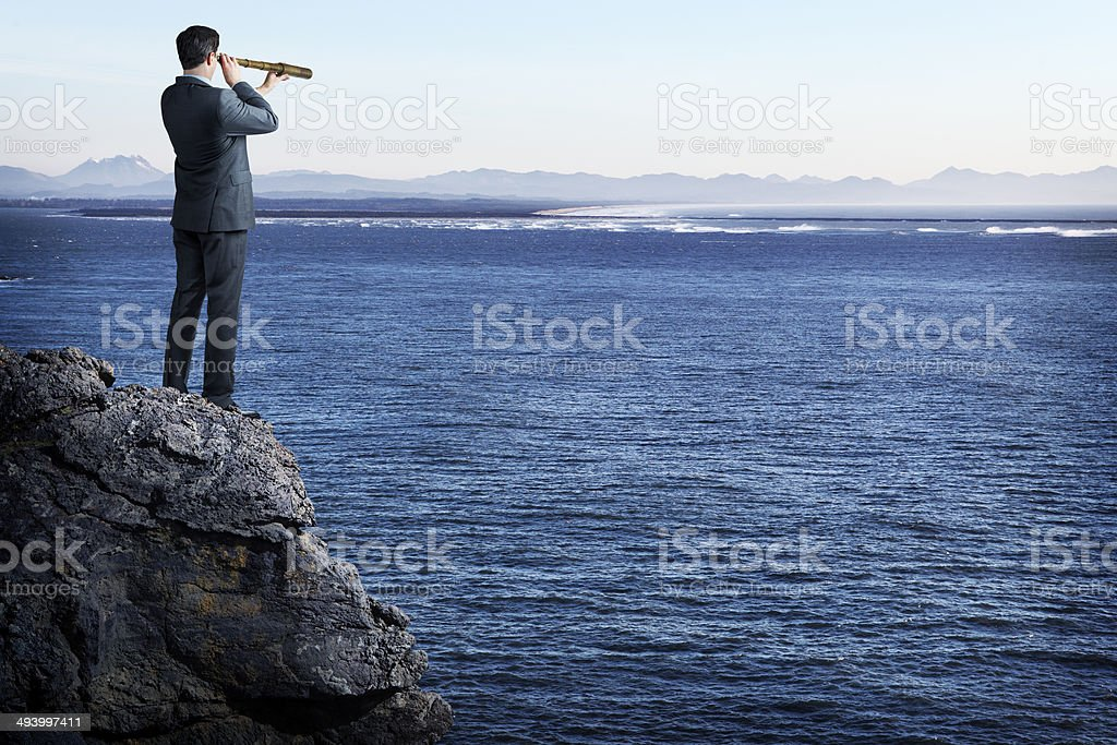 Businessman standing on cliff looking out to sea stock photo