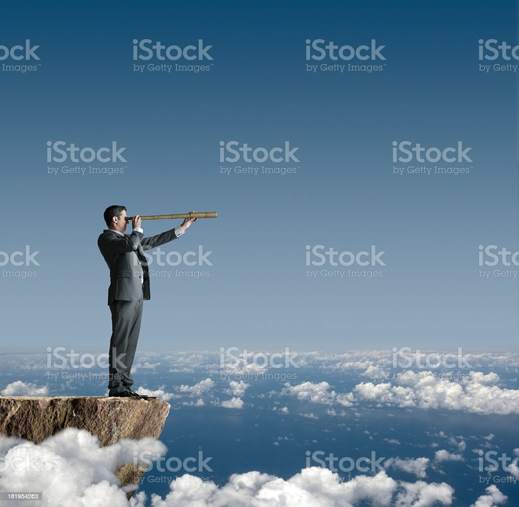Businessman Standing On Cliff Looking Through Spyglass stock photo
