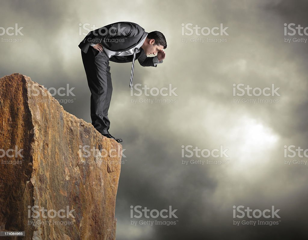 Businessman standing on edge of cliff looking down stock photo