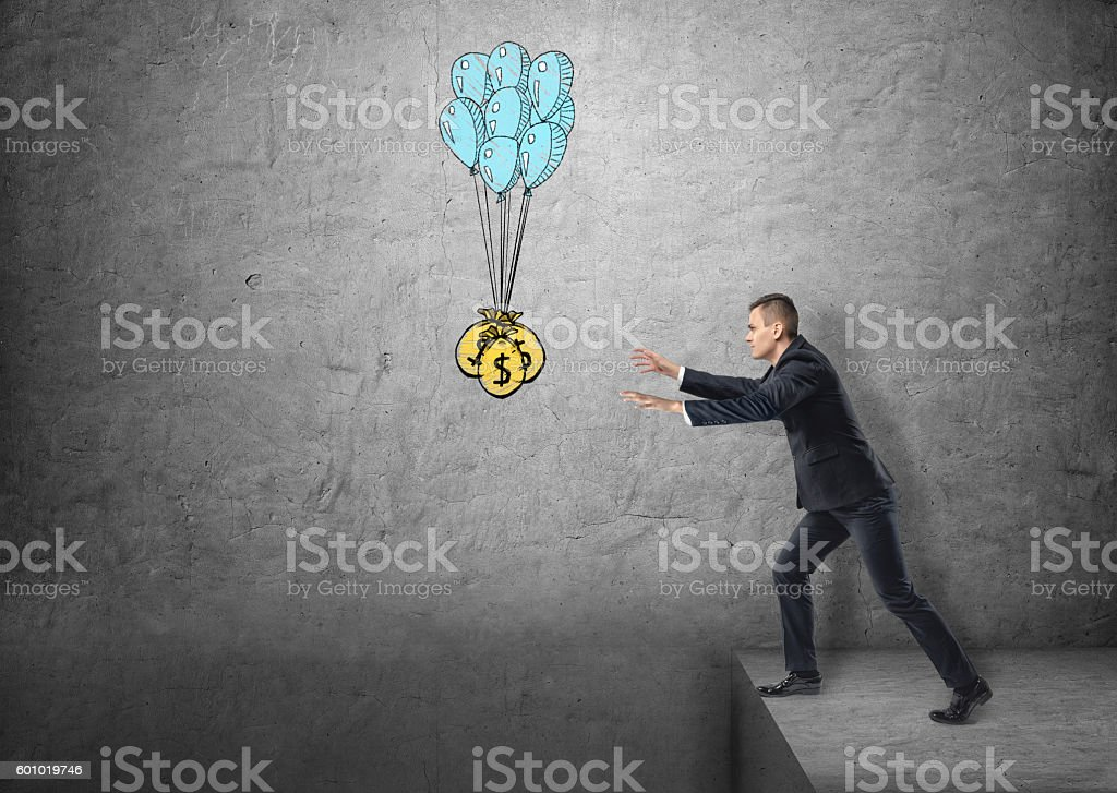 Businessman standing on edge reaching for sacks of money stock photo