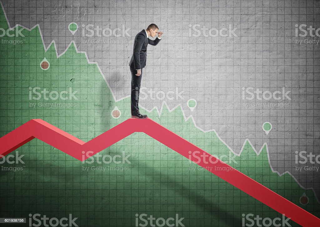 Businessman standing on falling diagram and peering into the future stock photo
