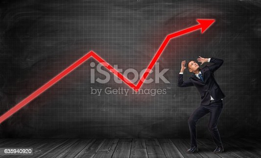 istock Businessman standing on floorboard and bending in fear under bright 635940920