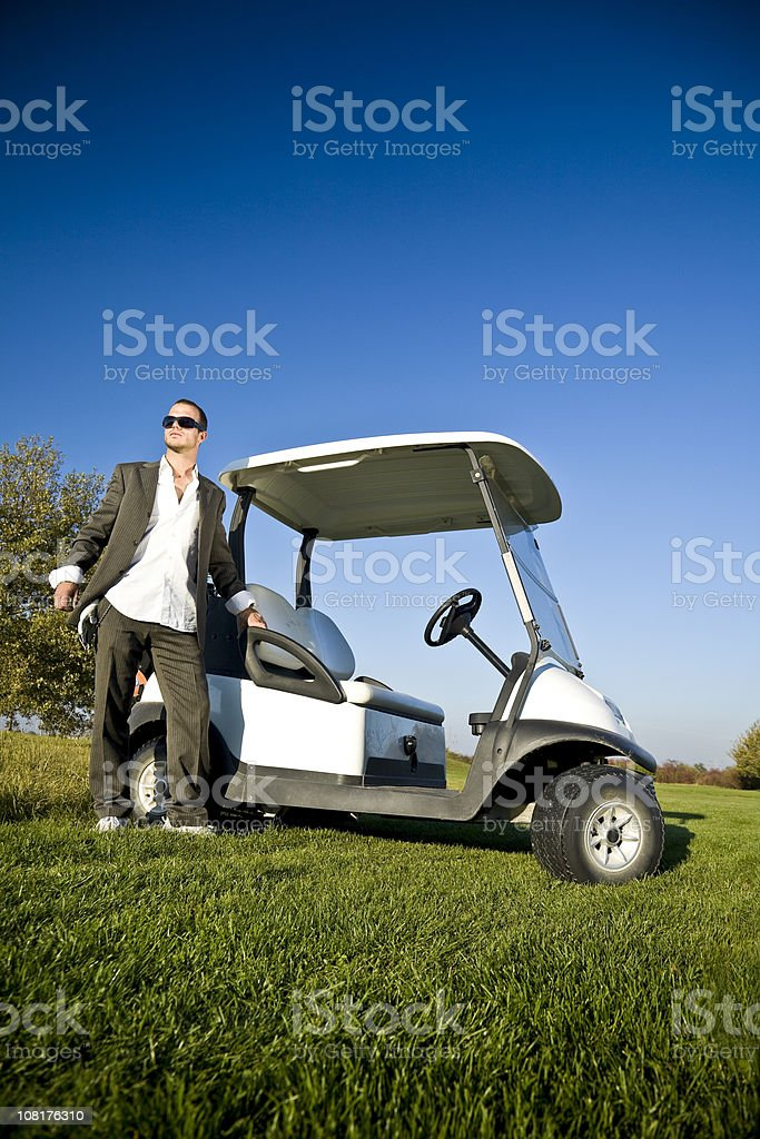 Businessman Standing on Green with Golf Cart royalty-free stock photo