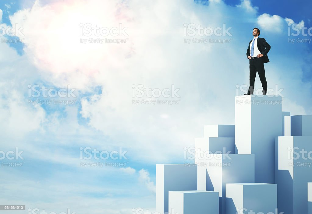 Businessman standing on highest cube stock photo