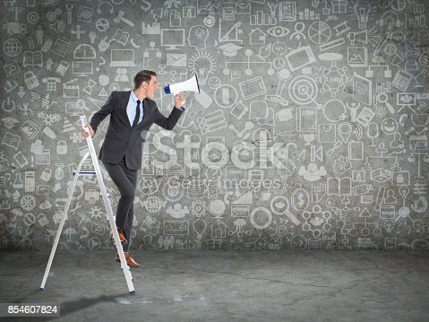 903659714 istock photo Businessman standing on ladder and holding megaphone 854607824