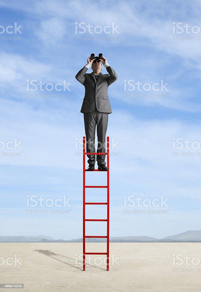 Businessman standing on ladder in desert looking through binoculars stock photo