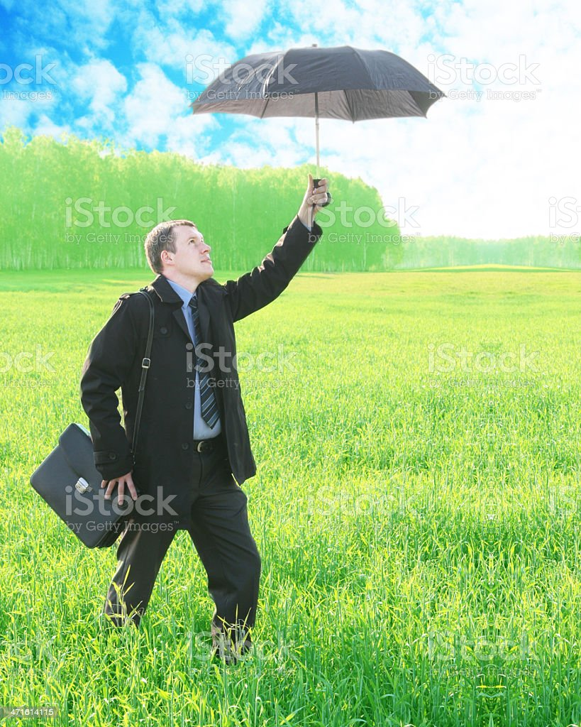 businessman, standing on meadow , holding an umbrella bright sunny day stock photo