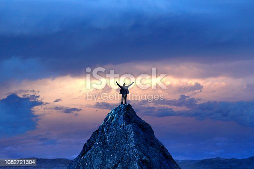 A silhouetted businessman stands on top of a mountain peak with outstretched arms in front of a dramatic sunset in the distance.