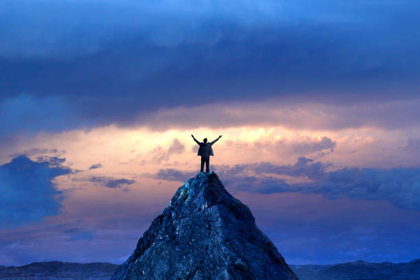 Businessman Standing On Mountain Peak A silhouetted businessman stands on top of a mountain peak with outstretched arms in front of a dramatic sunset in the distance. high up stock pictures, royalty-free photos & images