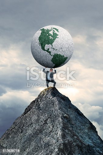 A business stands on a mountain top as he struggles to lift a large globe rotated towards the Western Hemisphere above him.  Stormy skies hover in the background.