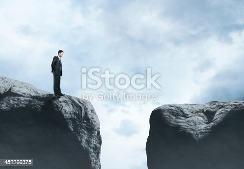 istock Businessman standing on one side of gap, looking across 452266375