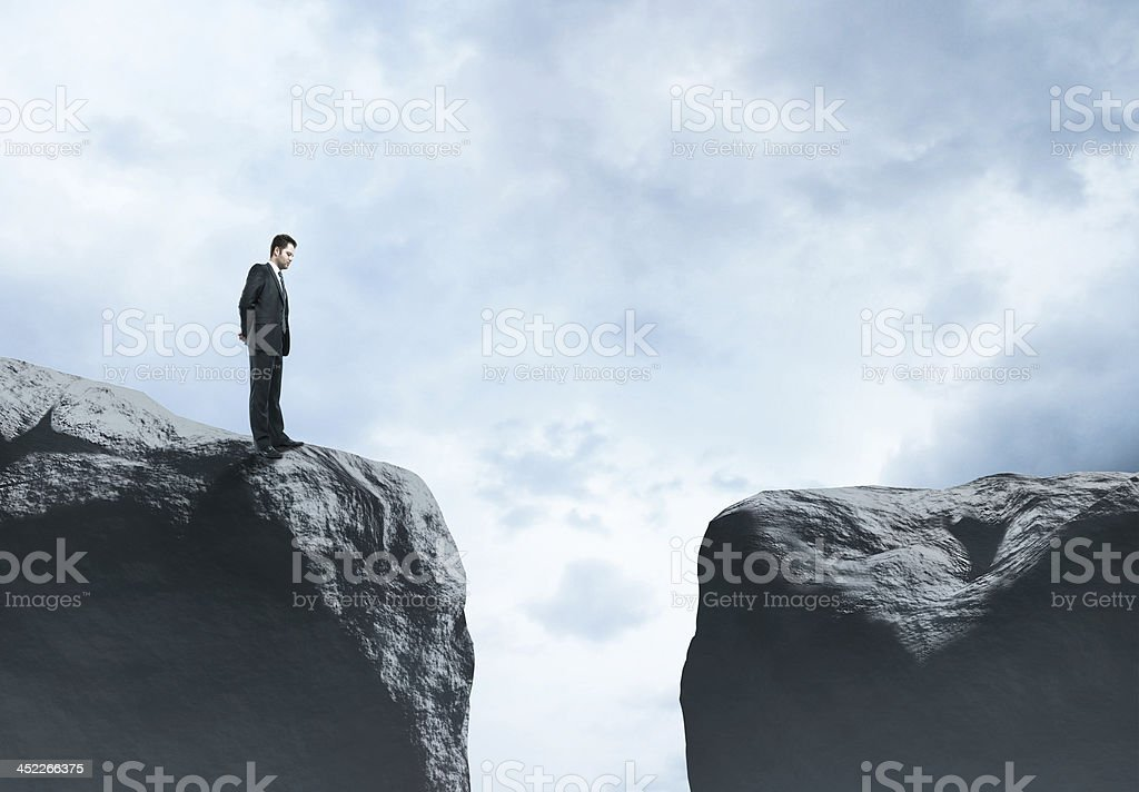Businessman standing on one side of gap, looking across stock photo