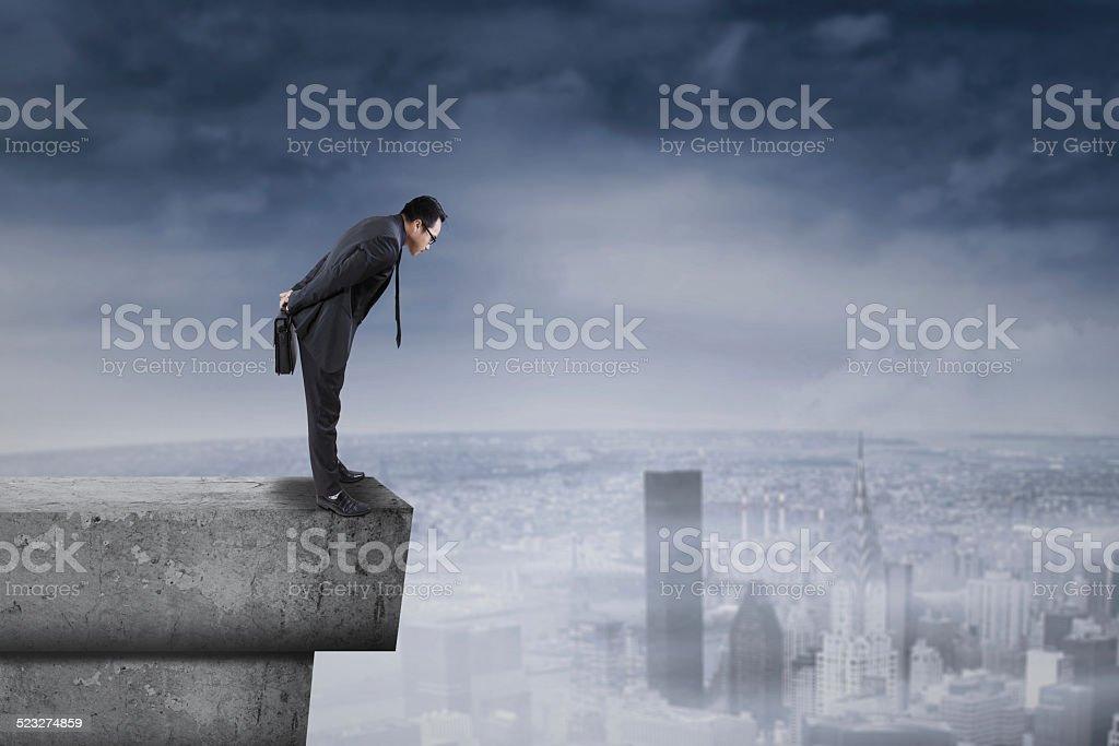 Businessman standing on rooftop and look down stock photo
