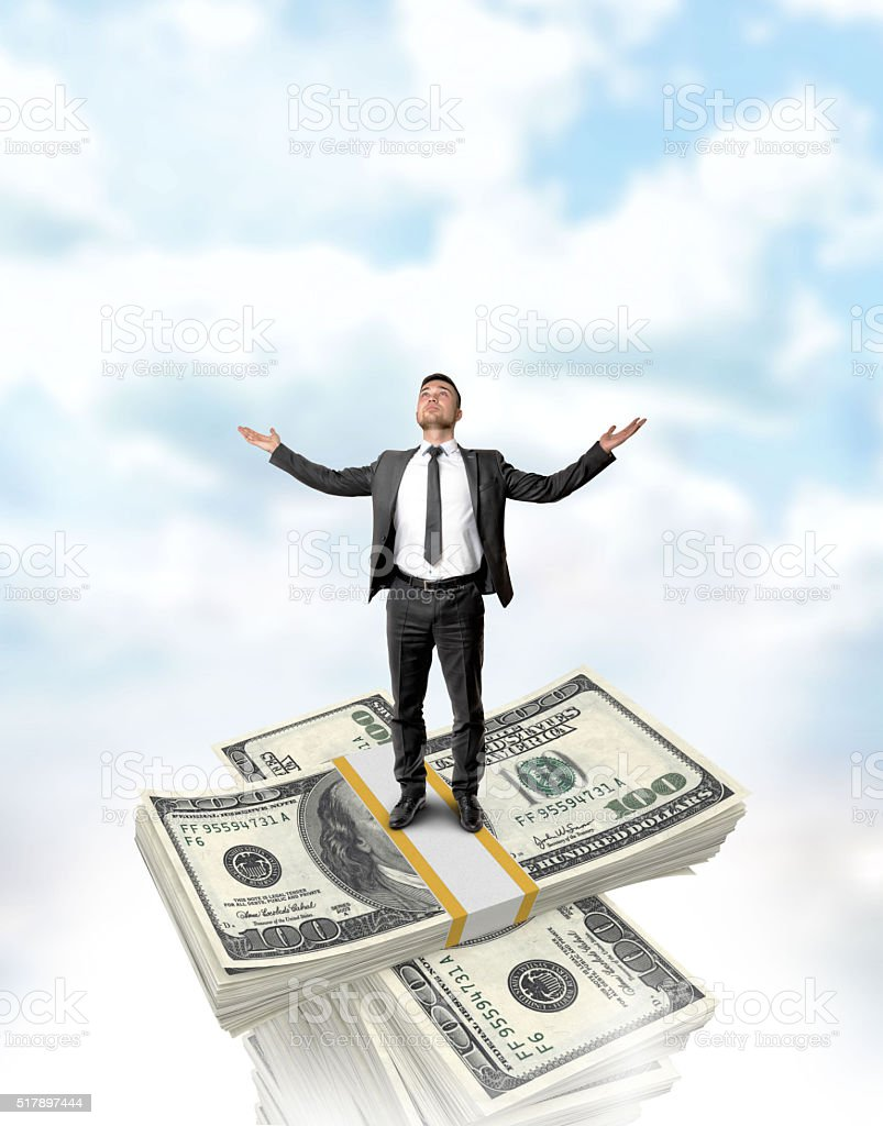 Businessman standing on the dollar stack top with a crossed stock photo