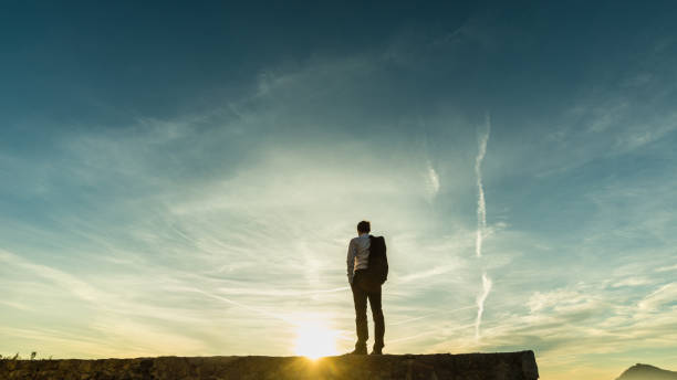 Businessman standing on the skyline on a wall stock photo