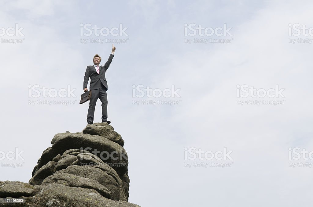 Businessman Standing on Top of Rock Mountain Raising Arm royalty-free stock photo