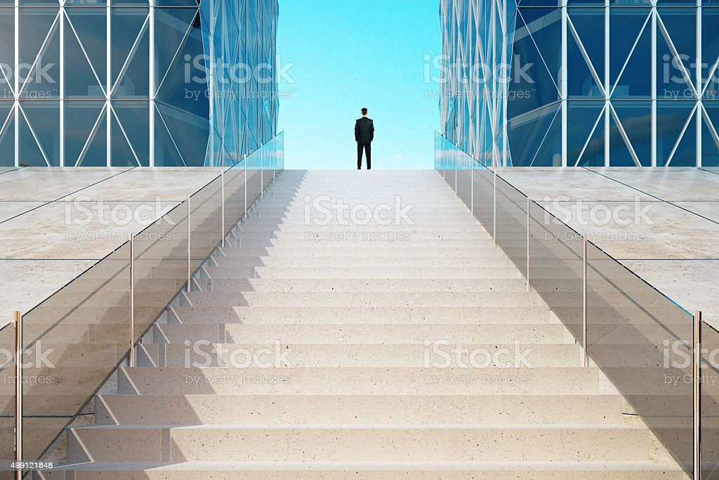 Businessman standing on top of the stairs near the modern stock photo