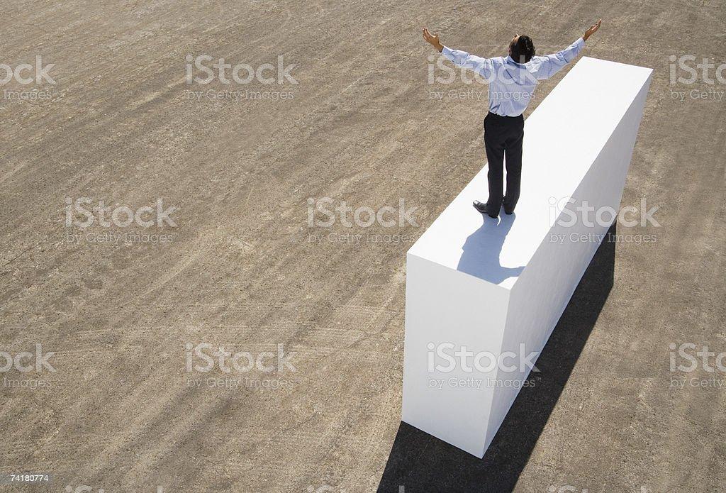 Empresário de pé com os braços para cima na parede foto de stock royalty-free