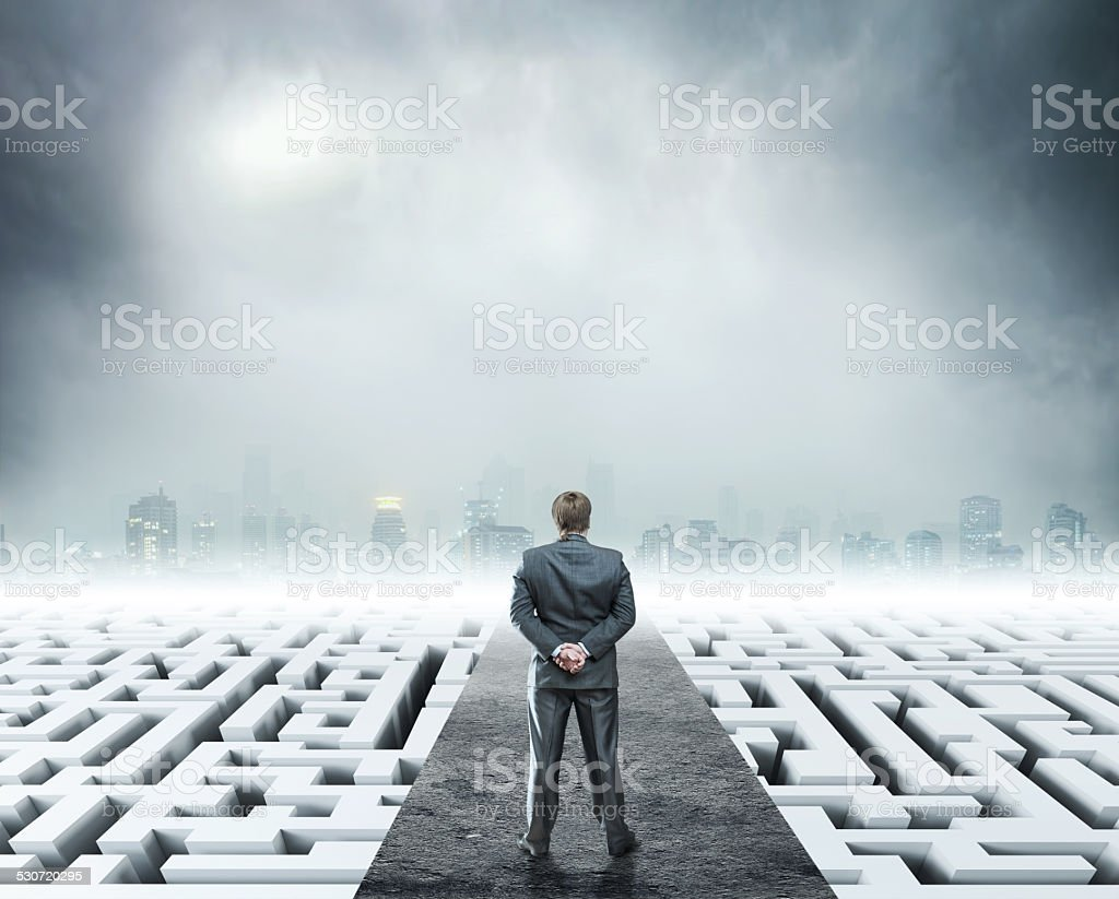 Businessman standing on white labyrinth stock photo